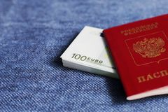 In the passport embedded the Euro banknotes. He Russian passport lies on a light blue background. In the passport embedded the Euro banknotes Royalty Free Stock Images