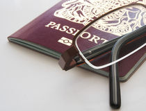 Passport and glasses. UK passport and glasses  on light background Royalty Free Stock Photography