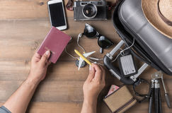 Passport in hand man with suitcase and accessories. On wood background, concept prepare to travel stock photo