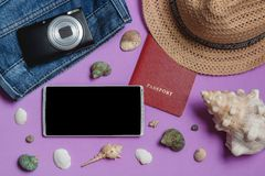 Passport, Jeans, Camera, Hat, Smartphone, Seashells on Lilac Background. Top View Travel Concept Mock up. Passport, Jeans, Camera, Hat, Smartphone, Seashells on Royalty Free Stock Images