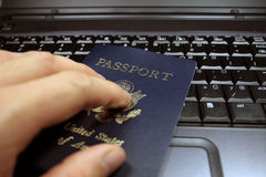 Passport on Laptop. A person holding passport on their laptop Stock Photo
