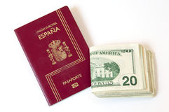 Passport and money. Spanish passport and U.S. banknotes on a white background Royalty Free Stock Images