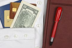 Passport, money, pen, notebook and Bank cards are on a white shi. The passport, money, pen, notebook and Bank cards are on a white shirt with sleeves Royalty Free Stock Photo