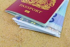Passport and money. UK biometric passports with euro notes laying on san Stock Images