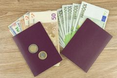 Passport and money on wooden table. Valid EURO banknotes. Illegal migration for money. Royalty Free Stock Image
