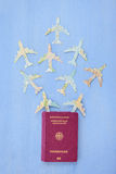 Passport with paper planes. German passport with Paper planes made from vintage maps on blue stock image