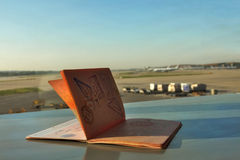 Passport with the planes on background. An opened foreign passport with the view of an airport Royalty Free Stock Photo