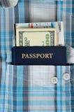 Passport in a pocket of shirt. Passport, money and boarding pass in a pocket of plaid shirt Royalty Free Stock Images