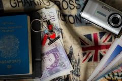 Passport and pound money with digital camera and guide travel on the wood table with England flag background. Brazillian passport with two pound papers money stock images