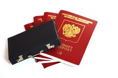 The passport of the Russian Federation. Biometric russian passports are laying around a miniature suitcase on a white background. The concept of travel and stock photos