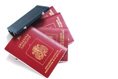 The passport of the Russian Federation. Biometric russian passports are laying around a miniature suitcase on a white background. The concept of travel and stock photography