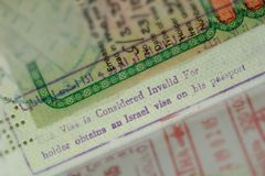 Passport stamp This Visa is Considered Invalid For holder obtains an Israel visa on his passport. In Arabian and English. Partially blurred background. Ban or royalty free stock images