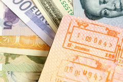 Passport with stamps on a different money Stock Photos
