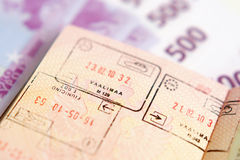 Passport with stamps on a money Royalty Free Stock Photos