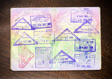 Passport and stamps on wood. En background Royalty Free Stock Image