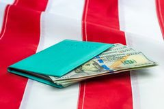 Passport stuffed with US dollars on a US flag. Close-up royalty free stock photo
