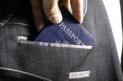 Passport in suit pocket. A passport being placed into a suit pocket Royalty Free Stock Images