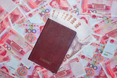 Passport with Thai baht on yuan currency background Royalty Free Stock Images