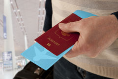 Passport and ticket in hand in airport Stock Photos
