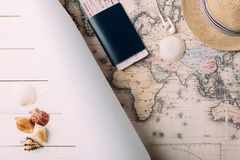 Passport with ticket on map. Passport with a ticket on a map, seashells on a wooden surface Stock Image