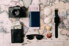 Passport with ticket and money on map. Flat lay of passport with ticket and money with watch on a map Stock Photos