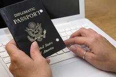 Passport to computers. Woman holding up passport while typing on computer as if it allows her access to internet or technology Royalty Free Stock Images