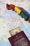 Passport to the World. A passport, some dollars, a map of countries and a toy train.  This is the dream of international travel and adventure Stock Image