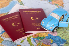 Passport, Toy Car and World Map. Vacation concept, view of world traveling map with blue toy car on and passport with the text Republic of Turkey in Turkish royalty free stock photography