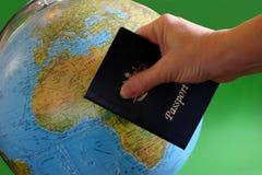 Passport for Travel. Hand holding passport in front of globe Stock Photo