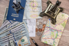 Passport with US currency and map, toy eiffel tower, check Royalty Free Stock Photo