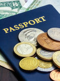 Passport with world currency. Blue passport with world currency on dark wood table Royalty Free Stock Photo