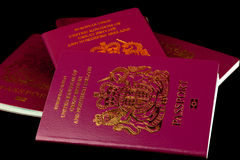 Passports on Black Background. A stack of old and new UK passports isolated on a black background Royalty Free Stock Images