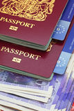 Passports, cards and money. UK biometric passports with EHIC cards laying on sterling money Stock Image