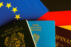 Passports on european and german flag. South africa, filipino, and irish travel document Passports on european and german flag Stock Image