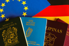 Passports on european and german flag. South africa, filipino, german and irish travel document Passports on european and german flag stock photography