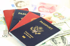 Multiple Passports Global Currencies. Multiple passports and currencies, concepts for travel, tourism, globalization, international finance royalty free stock photo