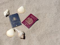 Passports on sandy tropical beach copyspace. Two passports australian/aussie and english/british on a sandy central american tropical beach surrounded by sea Royalty Free Stock Images