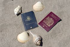 Passports on sandy tropical beach with shells. Passports in the sand with seashells, australian and english passport on sand on tropicla beach, costa rica Royalty Free Stock Photos