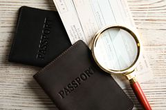 Passports, tickets and magnifying glass on table, top view. Travel agency. Passports, tickets and magnifying glass on wooden table, top view. Travel agency royalty free stock images