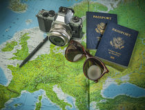 Passports to world travel. Passports for travel,camera and glasses on a map of the world stock image