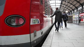 Passsengers on the railroad station platform. Wiesbaden, Germany - October 17, 2014: Passengers are boarding a suburb train of german railroad company DB at the stock video
