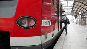 Passsengers on the railroad station platform. Wiesbaden, Germany - October 17, 2014: Some passengers are boarding a suburb train of german railroad company DB at stock footage