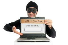 Password thief (phishing). A thief (dressed in black and eye-masked) pops up from behind a laptop's screen and hides the real URL by planting a fake one on it Stock Image