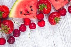 Pastèque, fraises et cerises sur le fond en bois Photos libres de droits