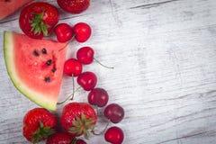 Pastèque, fraises et cerises sur le fond en bois Images libres de droits