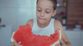 Pastèque rouge et jus de consommation appétissante heureuse de garçon coulant sous les dents banque de vidéos