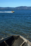 Past and current. Feed old boat and jet ski on blue background water mountains and sky Royalty Free Stock Photos