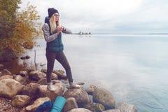 Past de Stylishly geklede blondesportvrouw een elektronische armband-pedometer aan die zich op de meerkust bevinden De herfstspor royalty-vrije stock foto