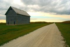 Past And Future. Looking down a country road where an old farm building stands, a reminder of past country life royalty free stock photography