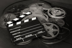 Past time movie symbol, home entertainment evocative objects. Heap of aged vintage super 8 mm movie reels, black clapper board selective focus detail Royalty Free Stock Photo